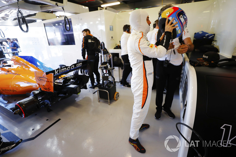 Fernando Alonso, McLaren, puts on his helmet in the team's garage