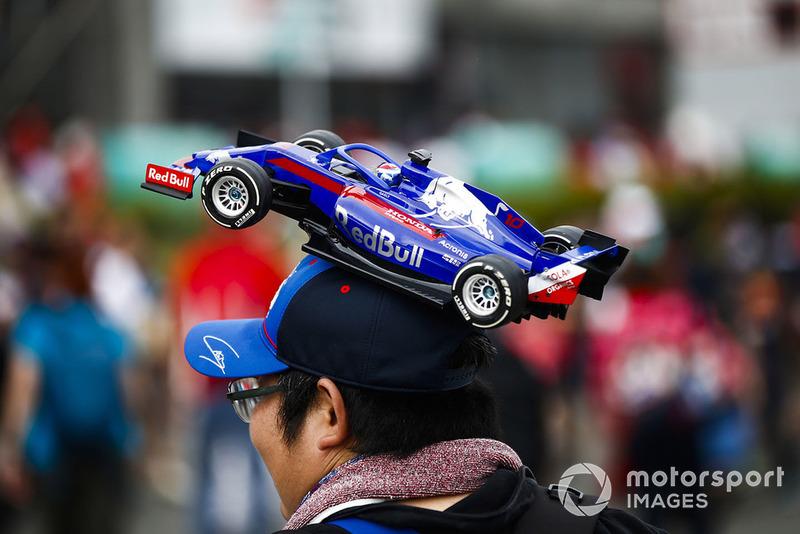 A fan with a Toro Rosso model car hat