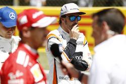 Fernando Alonso, McLaren, looks on as Valtteri Bottas, Mercedes AMG F1, Sebastian Vettel, Ferrari, are interviewed