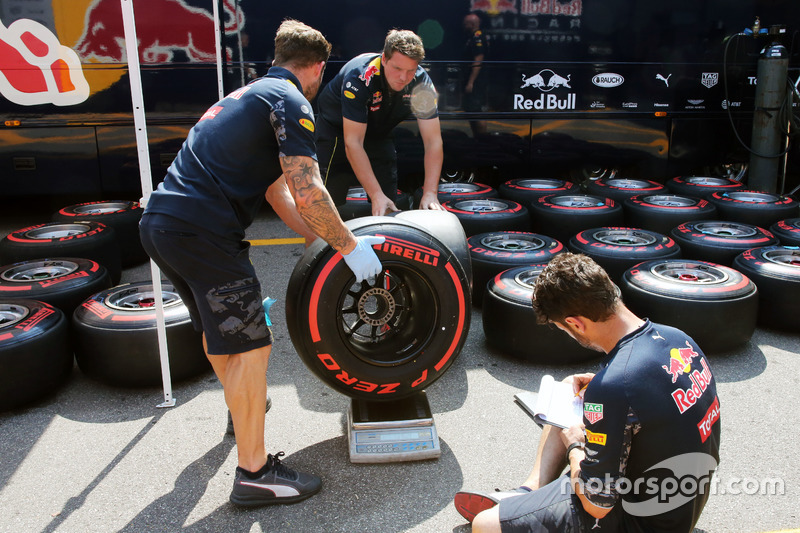 Red Bull Racing mechanics weigh a Pirelli tyre