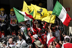 Ferrari team and mechanics celebrate in parc ferme with flags