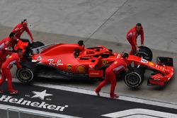 Des mécaniciens avec la Ferrari SF71H dans la voie des stands