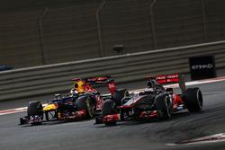 Jenson Button, McLaren MP4-27, voor Sebastian Vettel, Red Bull RB8