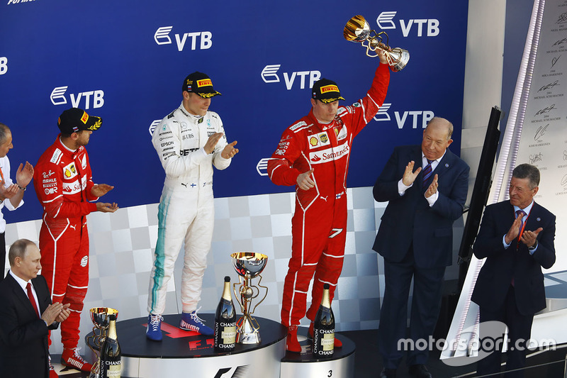 Third place Kimi Raikkonen, Ferrari, lifts his trophy alongside Race winner Second place Valtteri Bottas, Mercedes AMG F1 Sebastian Vettel, Ferrari