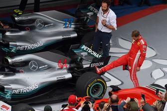Sebastian Vettel, Ferrari regarde le pneu arrière de la voiture de Lewis Hamilton, Mercedes-AMG F1 W09 dans le Parc Fermé