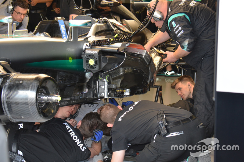 Mechanics of the Mercdes AMG F1 team working on the button of the cae