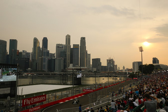 Fans watch LLewis Hamilton, Mercedes AMG F1 W09, in front of the Singapore skyline
