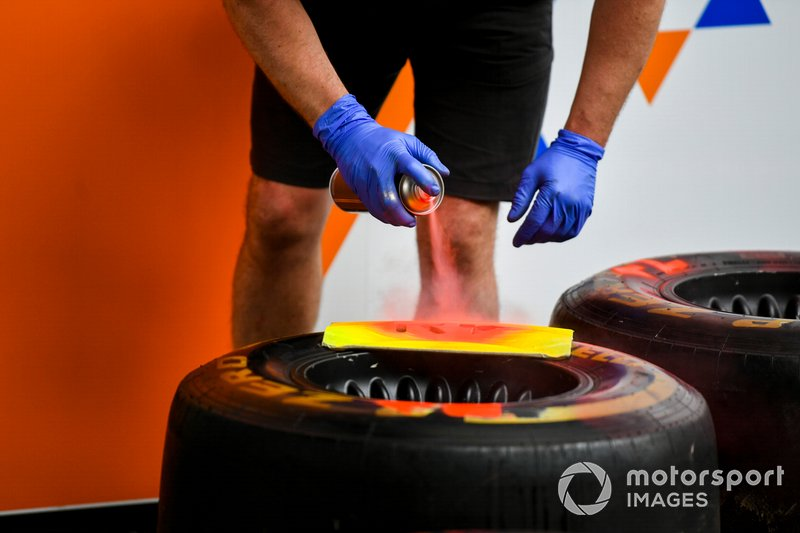 McLaren mechanic spray painting Pirelli tyre