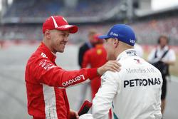 Sebastian Vettel, Ferrari, celebra su pole position, con Valtteri Bottas, Mercedes AMG F1