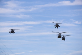 A pair of Boeing AH-64E Apache gunship helicopters and a pair of Boeing CH-47F Chinooks of the US Army fly over the grid