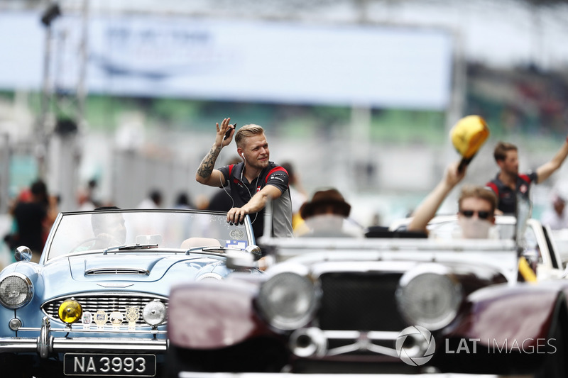 Kevin Magnussen, Haas F1 Team, waves to fans from an Austin Healey on the drivers parade