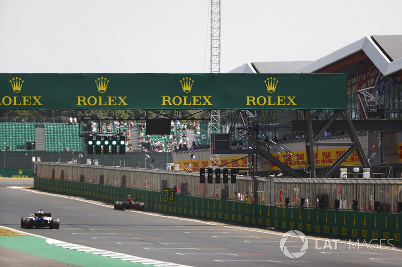 La monoposto di Max Verstappen Red Bull Racing RB14, parcheggiata accanto al murtetto mentre transita Lance Stroll, Williams FW41