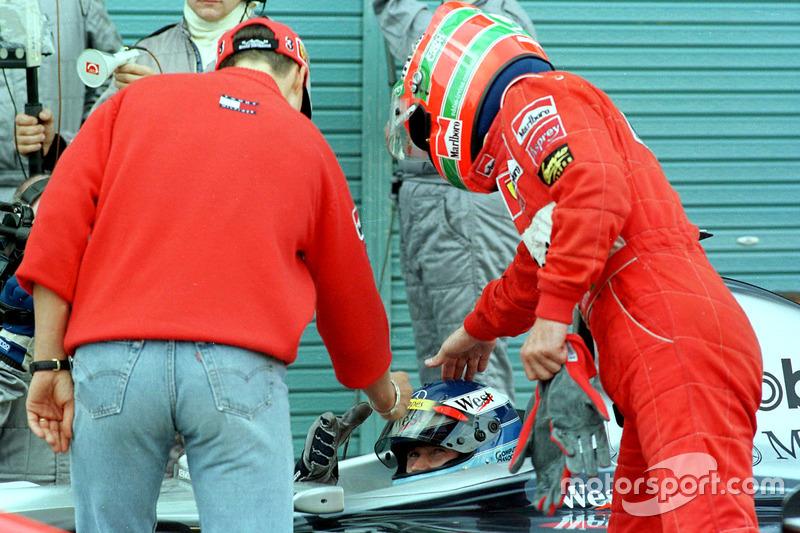 Pilotos de Ferrari Michael Schumacher y Eddie Irvine felicitan al nuevo campéon de Fórmula Uno Mika Hakkinen, McLaren