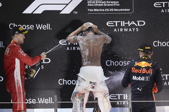 Lewis Hamilton, Mercedes AMG F1, 1st position, strips to the waist as Sebastian Vettel, Ferrari, 2nd position, and Max Verstappen, Red Bull Racing, 3rd position, spray him in celebration with Rose Water