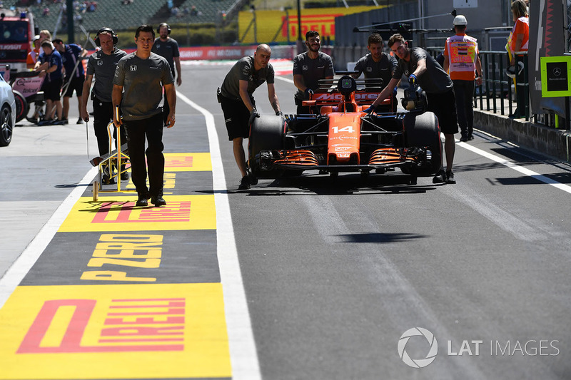 Mecánicos de McLaren empujan el auto de Fernando Alonso
