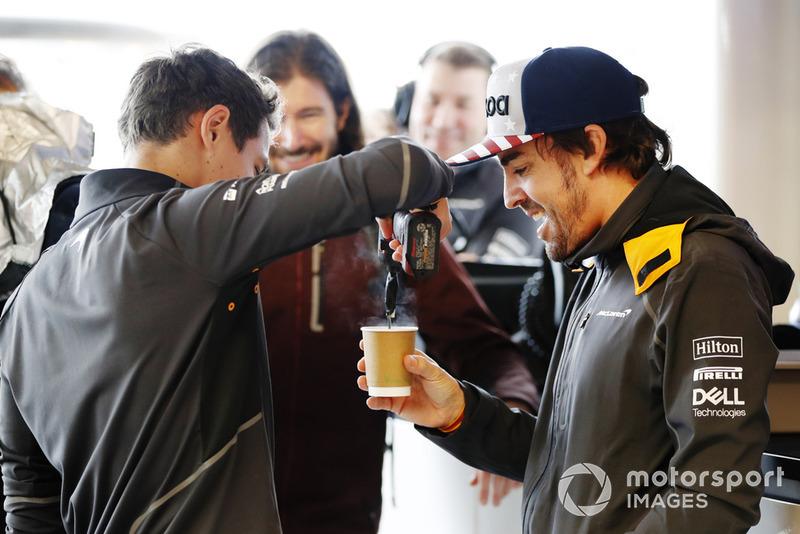 Lando Norris, McLaren, agita una taza de té con una herramienta eléctrica para Fernando Alonso, McLaren, mientras el conductor de IndyCar JR Hildebrand observa en el garaje