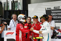 Winner Sebastian Vettel, Ferrari, is congratuled by second place Lewis Hamilton, Mercedes AMG F1, third place Kimi Raikkonen, Ferrari