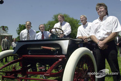 Dan Davis, Jackie Stewart (three-time Formula One Champion), Edsel B. Ford, Dale Jarrett (1999 NASCAR Winston Cup Champion), and John Force (ten-time NHRA Funny Car Champion) pose in front of a Ford 1901 Sweepstakes replica vehicle