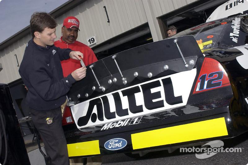 A crew member files down the rear spoiler of Ryan Newman's Alltel Ford Taurus