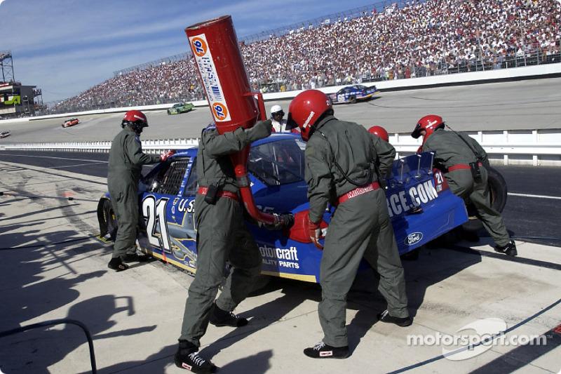 Miembros del equipo The Woods Brothers vestidos con trajes de vuelo de la Fuerza Aérea, dan servicio al Air Force Ford Taurus de Elliott Sadler