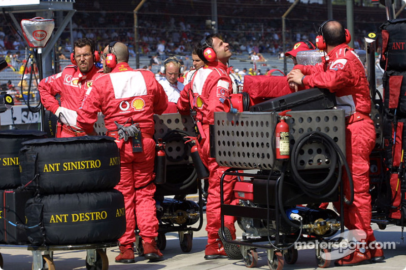 Ferrari crew members wait to go on the starting grid