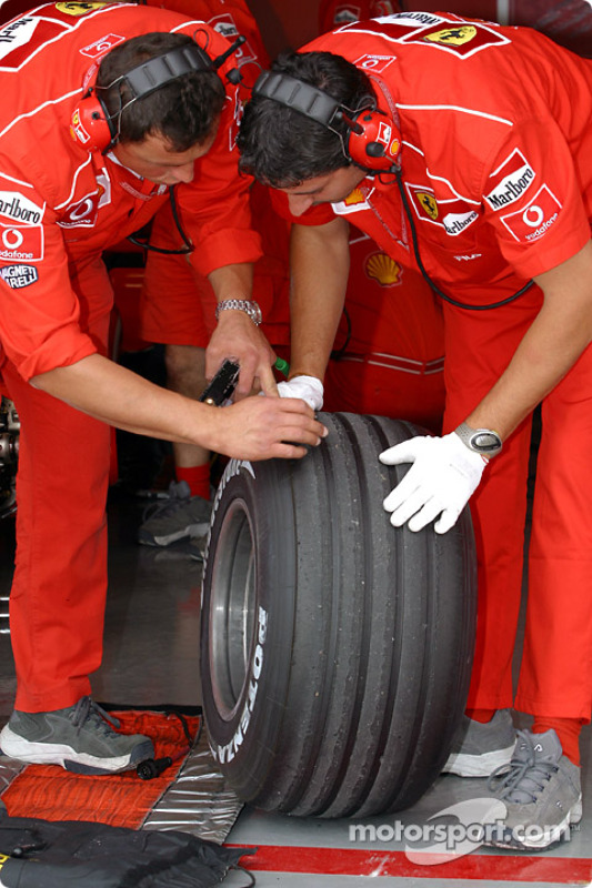 Miembros del equipo Ferrari preparan las llantas