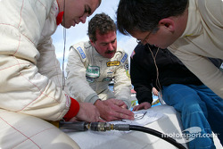 Defending GT champion Kevin Buckler shows the new drivers on his team the corners on a track diagram