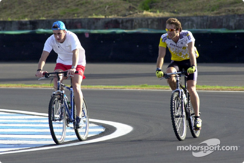 Fernando Alonso and Jarno Trulli ride their bicycle on the track