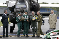 Antonio Pizzonia and Mark Webber exchange helmets with Apache pilots Major Mick Manninng and Captain Bill McPhee in front of a British Army Augusta Westland Apache