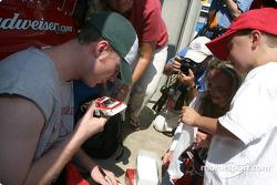 Dale Earnhardt Jr. signs his autograph on a #8 diecast car