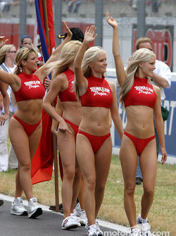 Hawaiian Tropic girls wave to the fans