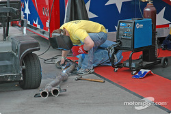 Crew member works on exhaust pipe