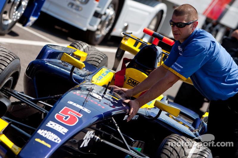 Un mécanicien Super Nova Racing pousse la voiture de Josef Kral Super Nova Racing dans le paddock
