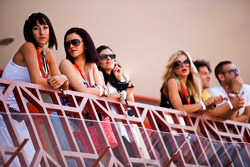 Girls watch the action from the pit lane