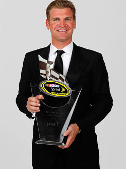NASCAR driver Clint Bowyer poses with his 10th place trophy