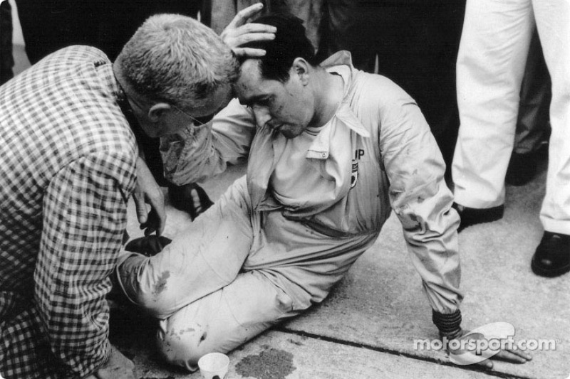 Jack Brabham takes a well-earned rest after pushing his Cooper-Climax half a mile to the finishing l