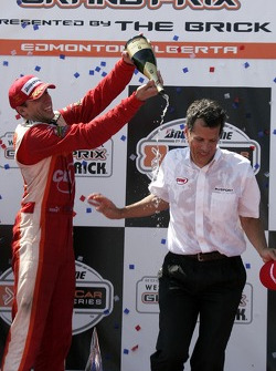 Justin Wilson helps team owner Carl Russo celebrate with champagne on the podium