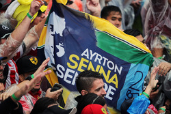 A Ayrton Senna banner with fans at the podium