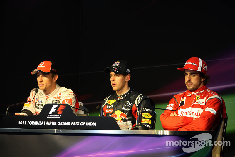 Second place Jenson Button, McLaren Mercedes, race winner Sebastian Vettel, Red Bull Racing, third p