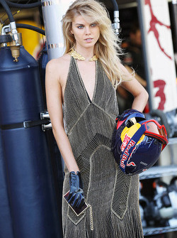 A glamorous woman with a Red Bull Racing mechanic's helmet
