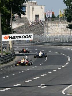 Formula Three cars in front of the stadium