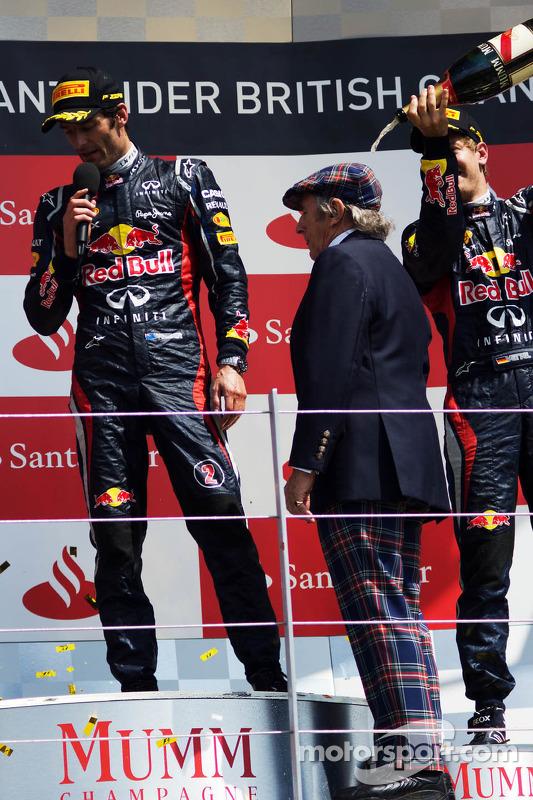 Sebastian Vettel, Red Bull Racing spuit champagne op Jackie Stewart, op het podium terwijl Mark Webber, Red Bull Racing het publiek entertaint