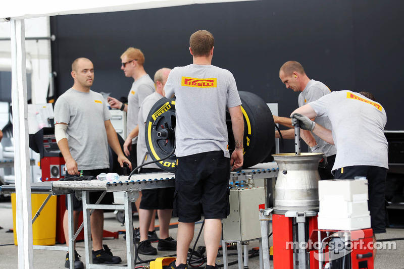 Pirelli engineers work on the tyres