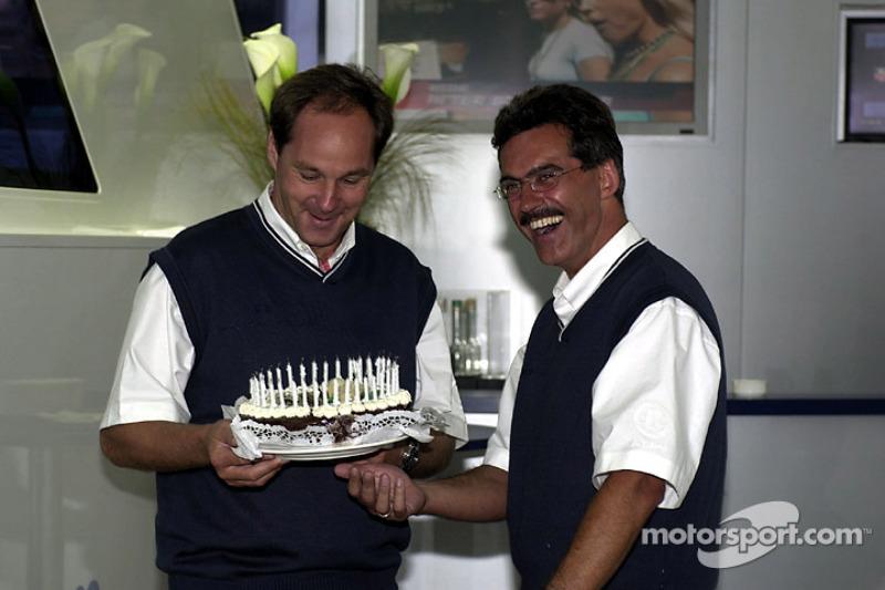 Hoofd van BMW Motorsport Dr. Mario Theissen geeft een verjaardagstaart aan Gerhard Berger