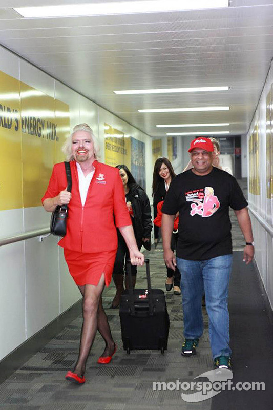 Sir Richard Branson werkt als stewardess tijdens een vlucht van Air Asia na een verloren weddenschap met Caterham F1 boss Tony Fernandes