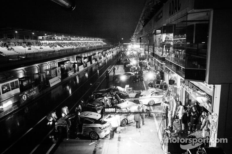 Een drukke pitstraat tijdens de onderbreking van de race
