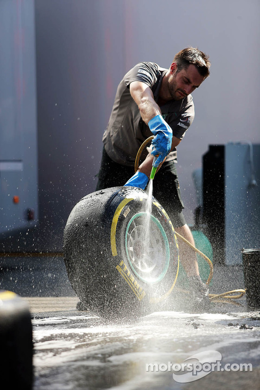 A Mercedes AMG F1 mechanic washes Pirelli tyres