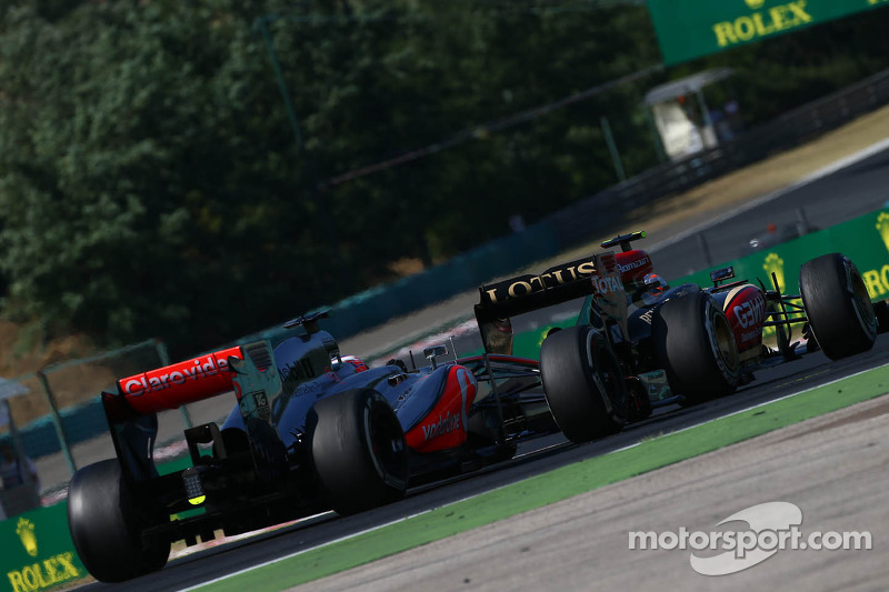 Jenson Button, McLaren MP4-28 and Romain Grosjean, Lotus F1 E21