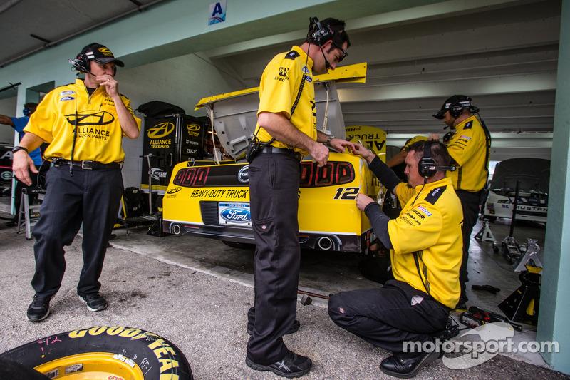 Penske Racing crew members repair some damage on the car of Sam Hornish Jr.
