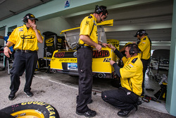 Penske Racing crew members repair some damage on the car of Sam Hornish Jr.